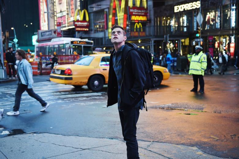 Fotograma de la serie MR. ROBOT. Rami Malek aparece rodeado de publicidad y marcas.